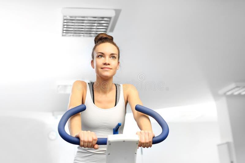 转动,在一辆固定式自行车的训练 健身房锻炼 免版税图库摄影