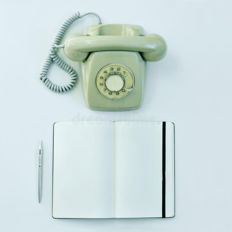 转台式电话、笔和空白的笔记薄在桌上 免版税库存图片