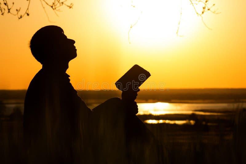 转向上帝的人剪影与希望、信念的概念和灵性 免版税库存照片