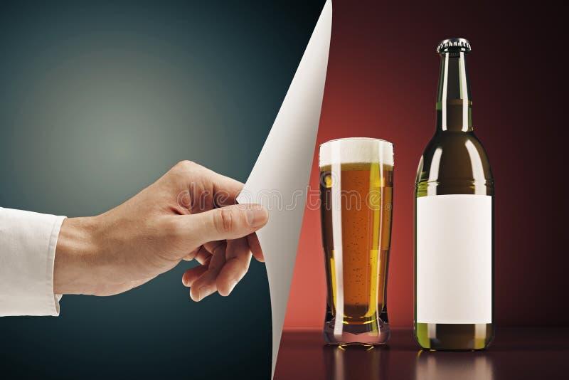翻转啤酒页的手 免版税库存图片