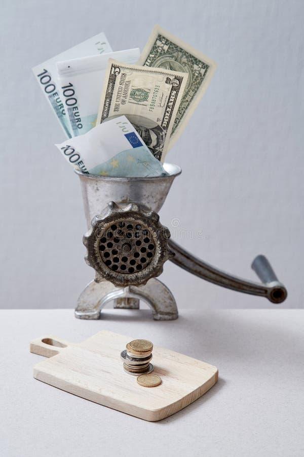 转淡和银行或者金融危机 通货膨胀和贬值金钱概念 研磨机研的钞票到硬币里 库存图片