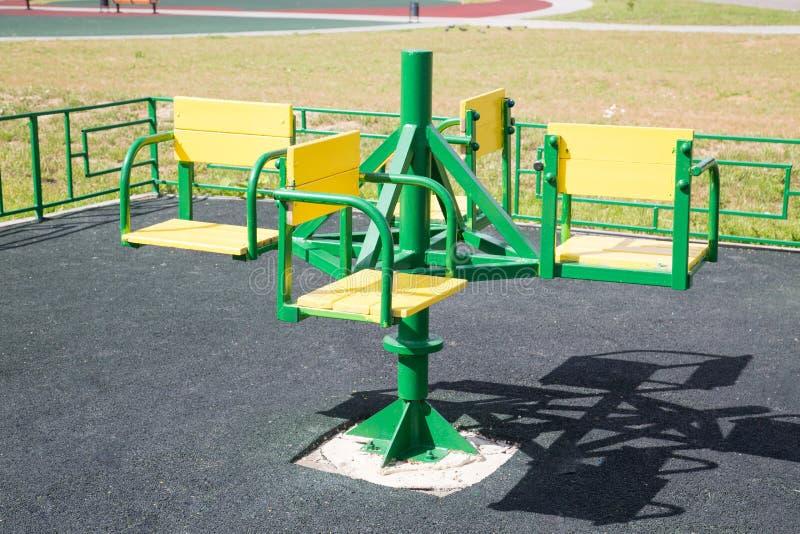 转盘儿童的在操场的金属绿色有橡胶处理的涂层的 免版税库存照片