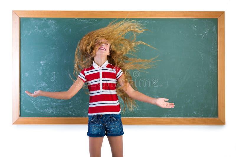 翻转长的头发的滑稽的学生女孩在学校 免版税图库摄影