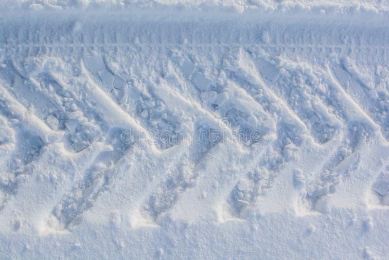 轮子印刷品在雪的 库存照片
