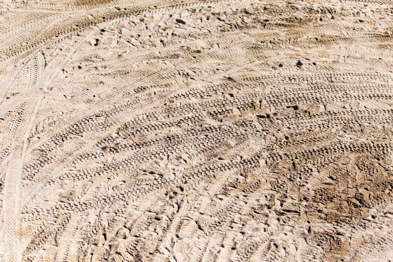 轮子踪影在沙子的作为背景 库存照片
