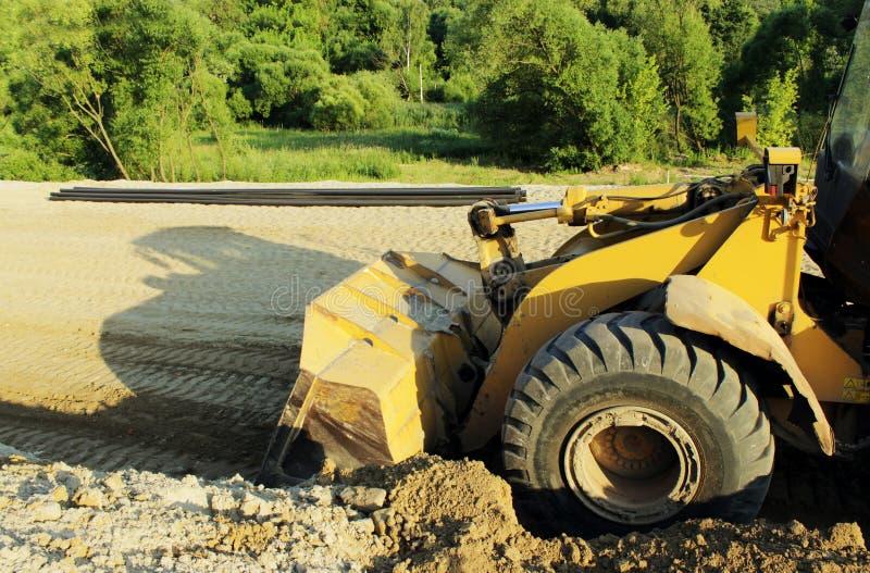 轮子铲起的沙子推土机机器在eathmoving在建造场所运转 库存照片