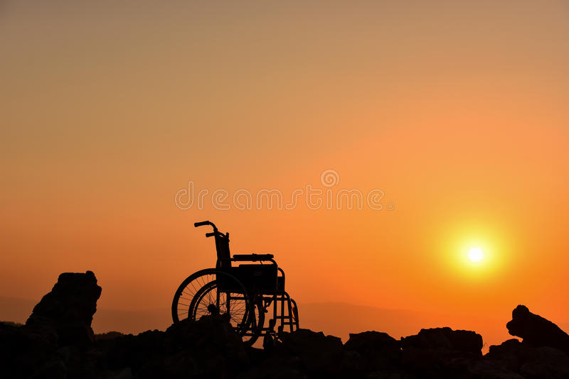 轮椅剪影和日出 库存图片