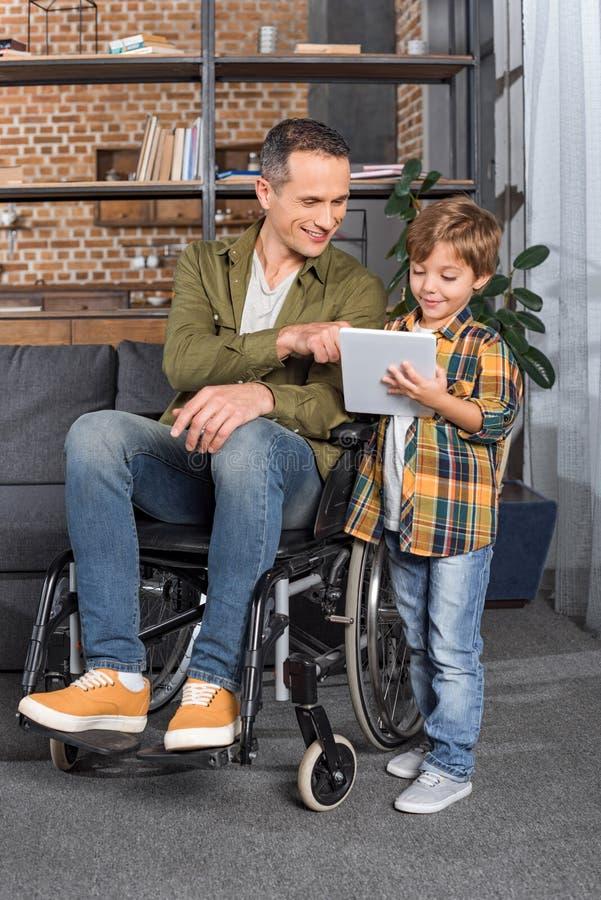 轮椅和一起使用片剂的小儿子的微笑的人 库存图片