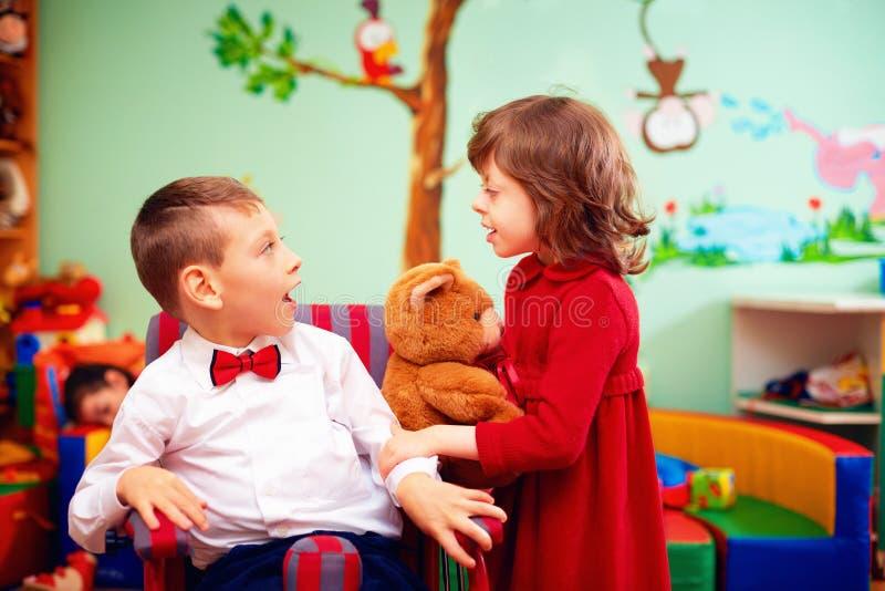 轮椅和夫人的逗人喜爱的矮小的绅士在度假在孩子的幼儿园与特别需要 免版税图库摄影
