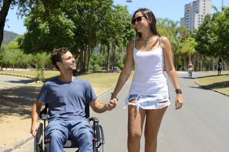 轮椅和女朋友的人 库存照片