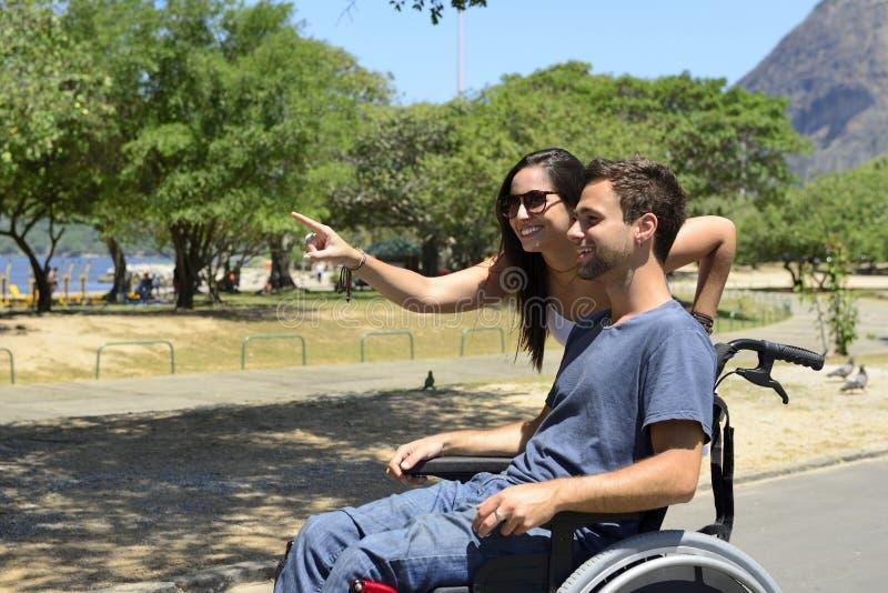 轮椅和女朋友的人 库存图片