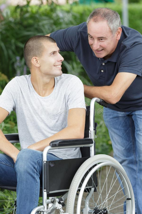 轮椅和父亲的儿子步行的 免版税图库摄影