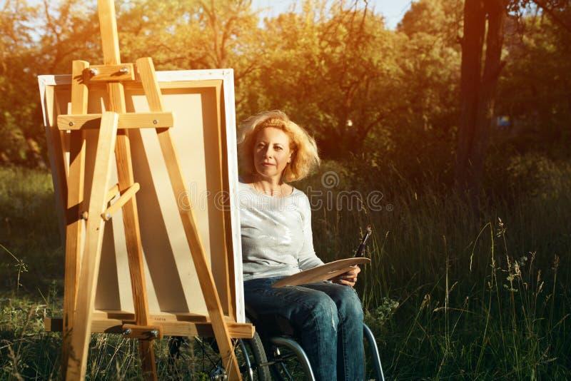 轮椅图画的妇女在外面画架 图库摄影