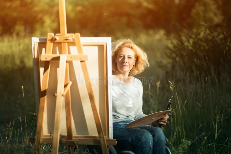 轮椅图画的妇女在外面画架 库存照片
