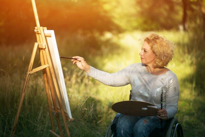 轮椅图画的妇女在外面画架 库存图片