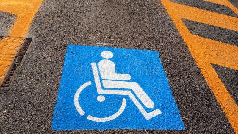 轮椅在黑暗的柏油路街道背景障碍停车场的障碍标志 图库摄影