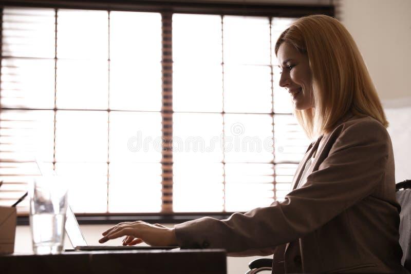 轮椅工作的妇女与膝上型计算机在桌上 库存图片