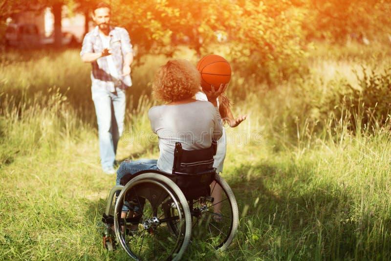 轮椅戏剧的妇女与与户外她的家庭的球 库存照片