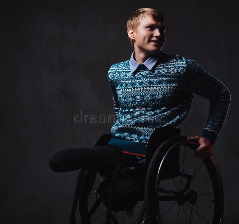 轮椅的一个人在灰色背景 免版税库存图片