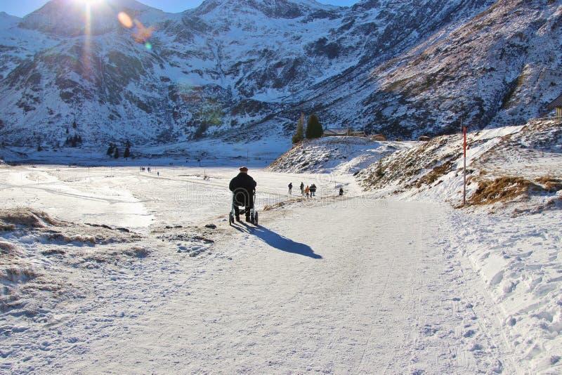 轮椅的一个老人享受冬天风景 奥地利,欧洲图片
