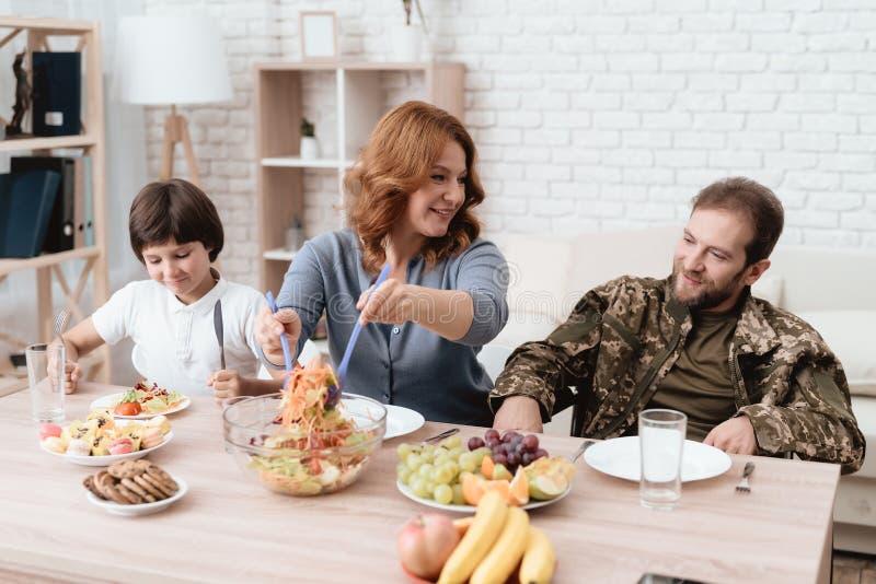 轮椅的一个退伍军人与他的家庭用餐 制服的一个人坐在厨房用桌上 库存照片