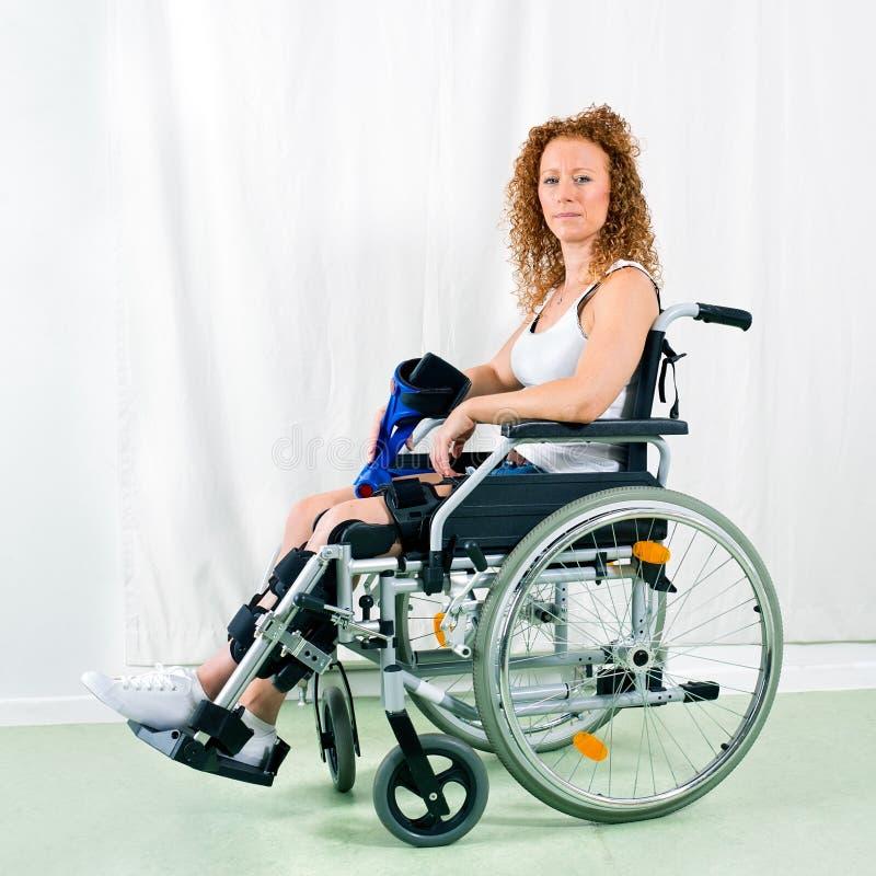 轮椅的严肃的妇女看照相机 免版税库存图片
