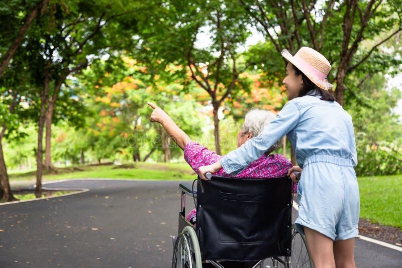 轮椅的亚裔资深妇女有走的绿色自然,祖母小孩女孩支持的残疾祖父母的和 免版税库存图片