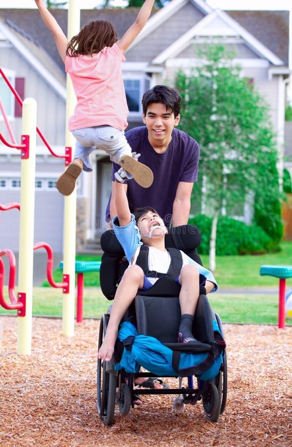 轮椅的享用残疾的男孩观看朋友使用在同水准 免版税库存图片