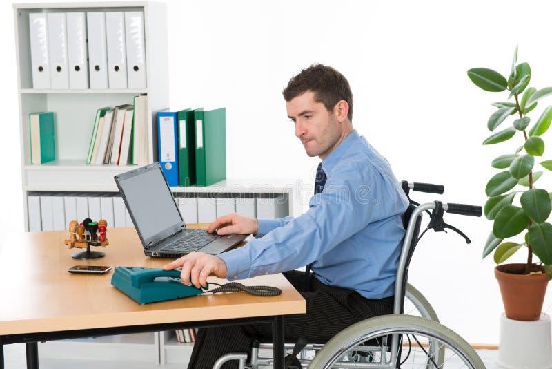 轮椅的人在办公室 库存照片