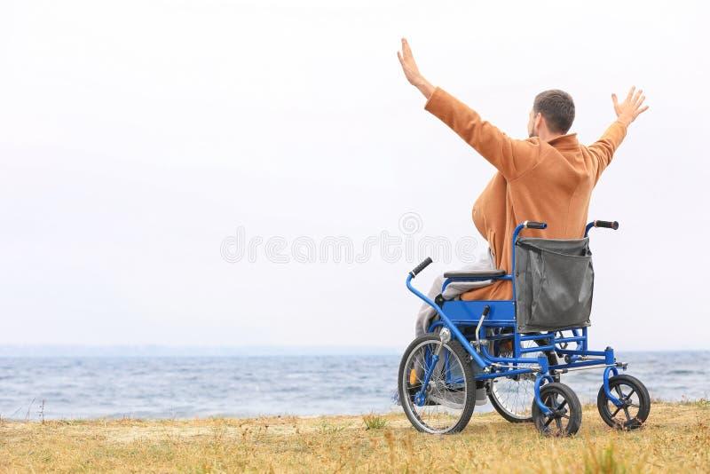 轮椅的人在海 免版税库存照片
