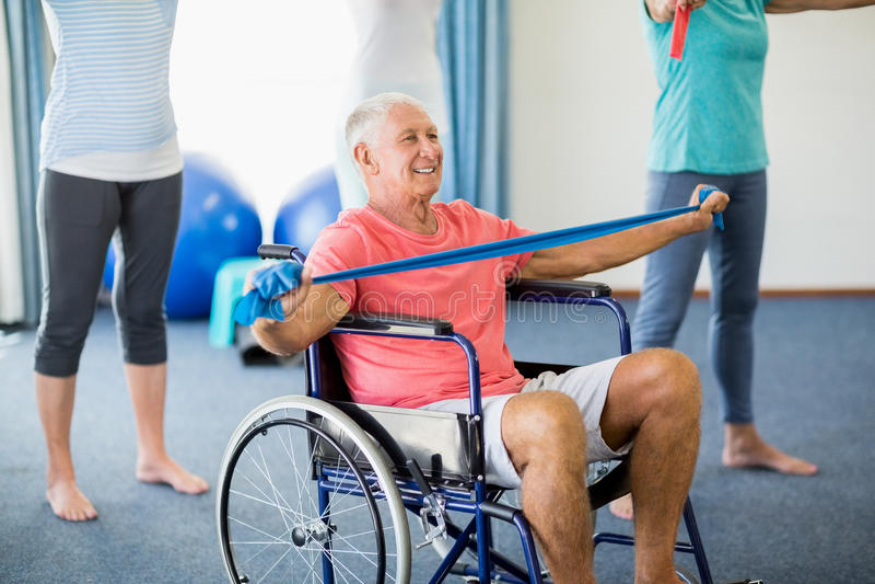 轮椅的前辈行使与行使的带 免版税库存照片
