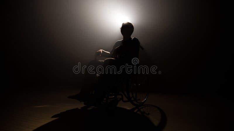 轮椅的剪影黑暗的人在奥秘阶段 录影生产和摄影与影片带领了光在背景 免版税图库摄影