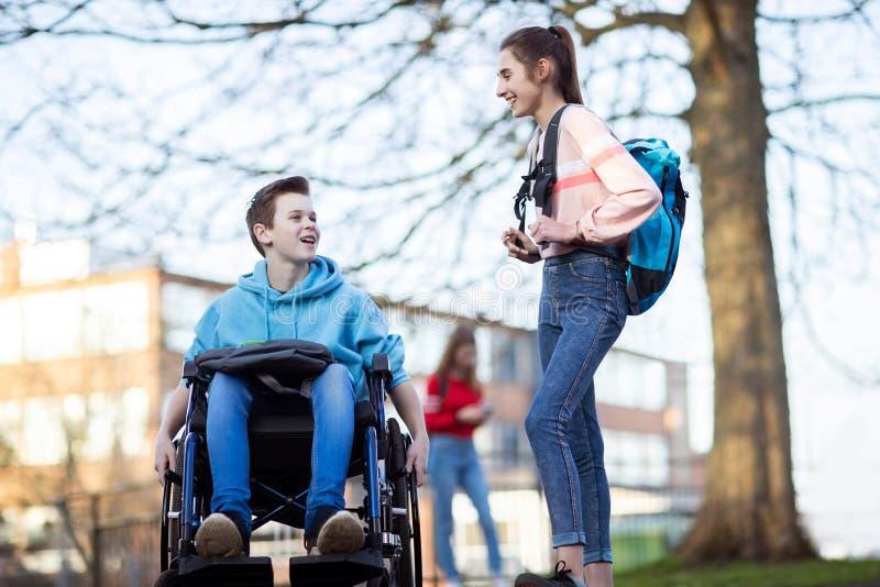 轮椅的十几岁的男孩谈话与女性朋友,他们离开高中 免版税库存图片