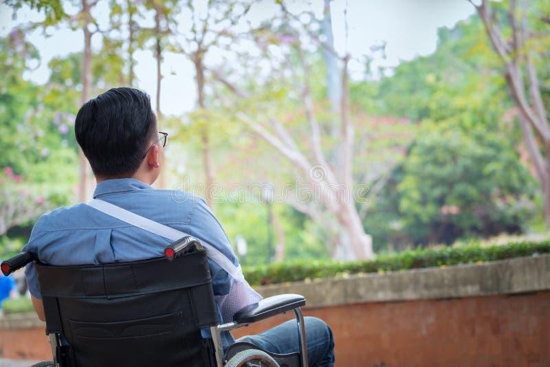 轮椅的单独年轻残疾人在公园,患者是r 免版税库存图片