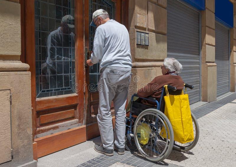 轮椅的妇女在街道上 免版税库存图片