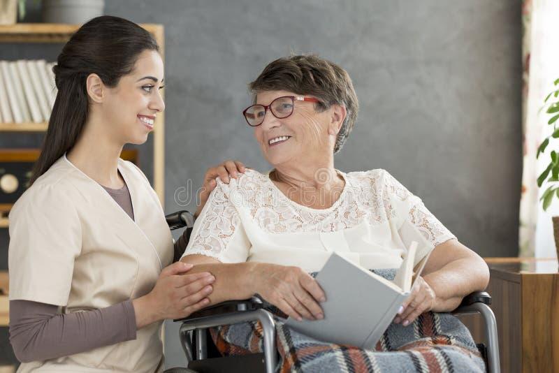 轮椅的妇女有护士的 免版税库存照片