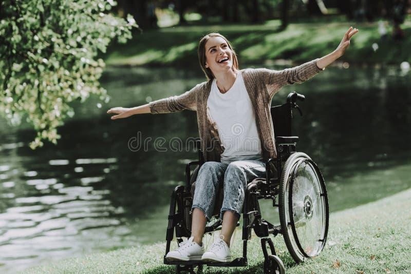 轮椅的年轻微笑的女孩在湖附近的公园 库存图片