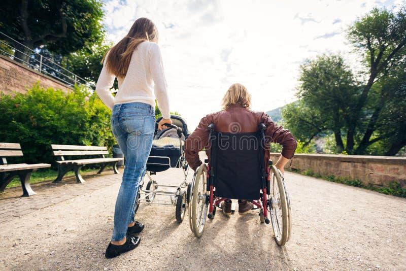 轮椅的年轻父母有婴儿车的在公园 图库摄影