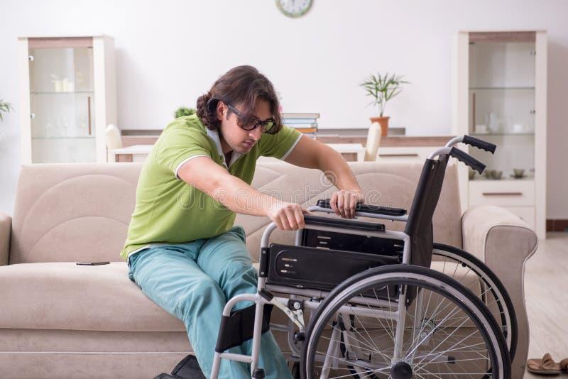 轮椅的年轻男生在家 免版税库存图片