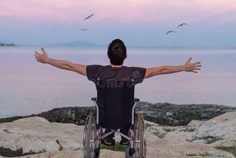 轮椅的废人在日落的海滩附近 免版税库存图片