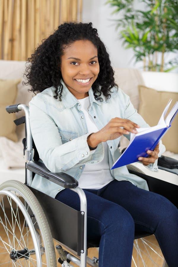 轮椅的微笑的年轻女人 免版税库存图片