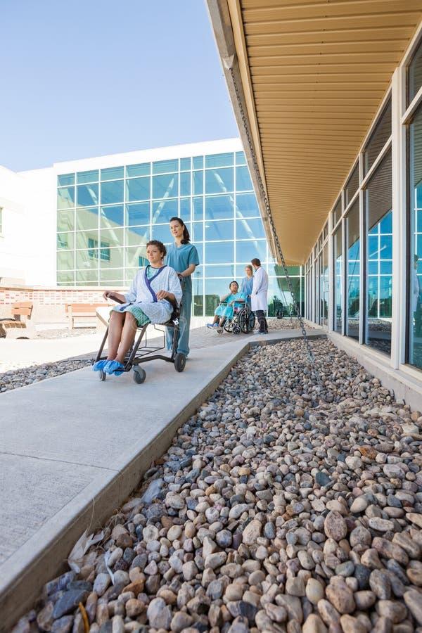 轮椅的患者有医疗队的在 免版税库存照片