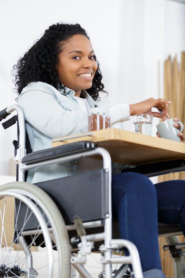 轮椅的愉快的妇女在家吃晚餐的 免版税图库摄影
