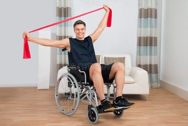 轮椅的有残障的人行使与抵抗带的 图库摄影