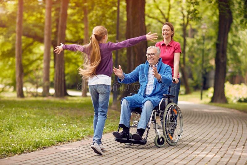 轮椅的欢迎残疾的祖父他的孙女 免版税库存照片