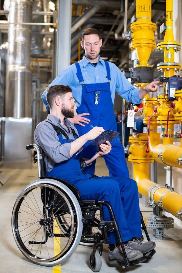 轮椅的残废工人在工厂和同事 库存照片