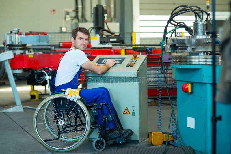 轮椅的残废工人在工厂和同事 免版税库存图片