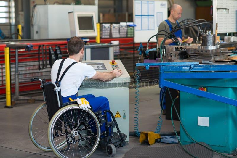 轮椅的残废工人在工厂和同事 图库摄影