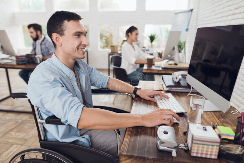 轮椅的残疾人在办公室工作在计算机 免版税库存图片