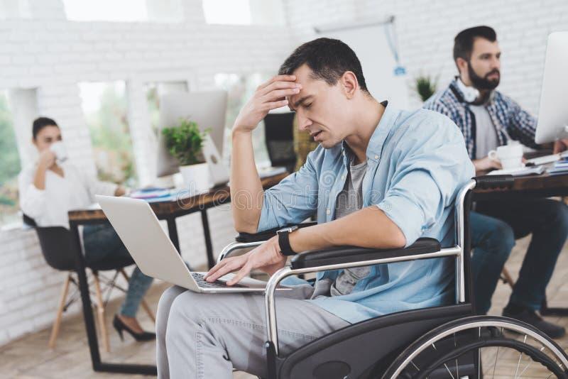 轮椅的残疾人在办公室工作 他周道地坐 图库摄影